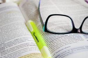 Bild mit Brille auf Buch mit Textmarker