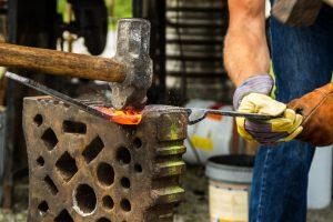 Bild mit Mann der auf dem Amboss schmiedet - Starten Sie Ihren Kurs zum Industriemeister Metall Samstags
