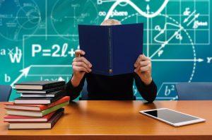 Bild vom Lernen lernen. Lernender sitzt mit einem Buch am Schreibtisch und hinter ihm befindet sich eine Tafel.
